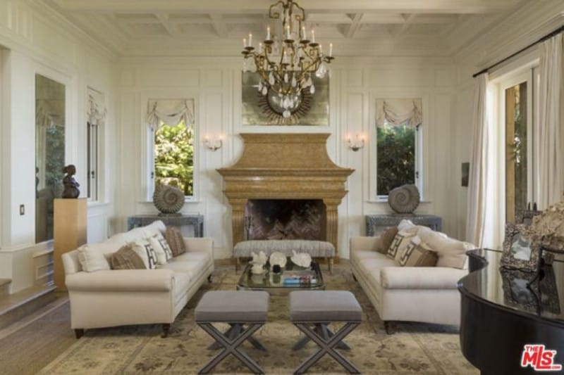 This Mediterranean living room features classy rug and seats along with a glamorous chandelier and fireplace.