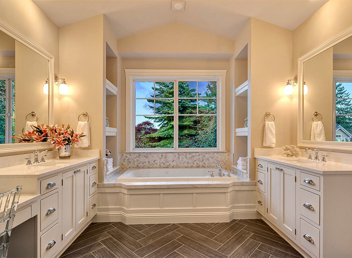 Facing his and her vanities along with built-in shelves flanking the soaking tub creates perfect symmetry to this primary bathroom.