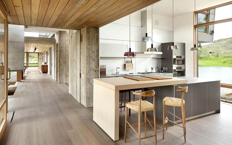 An open kitchen decorated by hanging pendant lights over a breakfast island with wood accent and a pair of counter stools. It is situated along the corridor of the house.