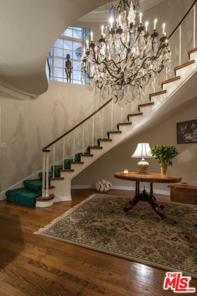 This home entry features a staircase with green walls lighted by a glamorous chandelier.
