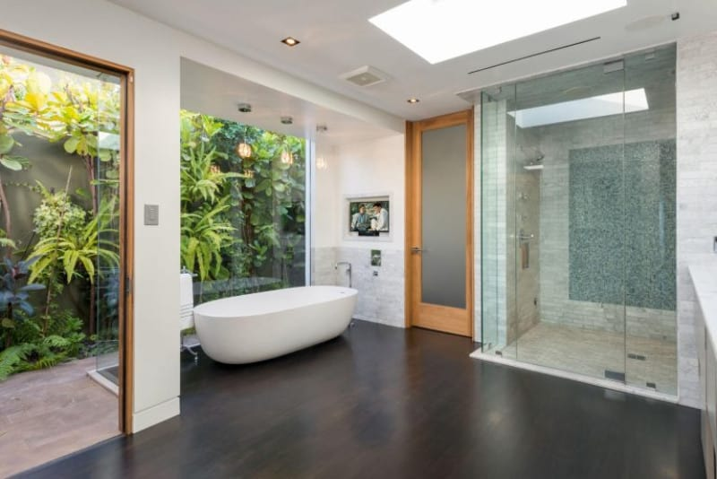 This simple master bathroom offers a walk-in shower and a freestanding tub set on a hardwood flooring. There's a glass window near the tub overlooking the beautiful plants outside.