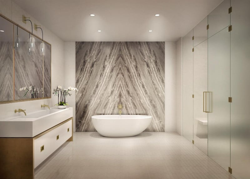 A glamorous master bathroom featuring an attractive wall near the freestanding tub. The room also boasts a walk-in shower room and a large sink area.