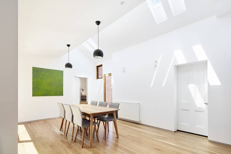 Spacious dining room offers a wooden dining table with gray tufted chairs. It is lighted by a pair of black pendants along with skylights fitted on the vaulted ceiling.