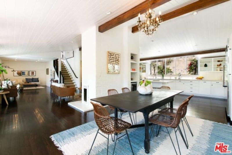 This dining space showcases a white shiplap vaulted ceiling lined with natural wood beams. It has a wooden dining set that sits on a striking blue rug.