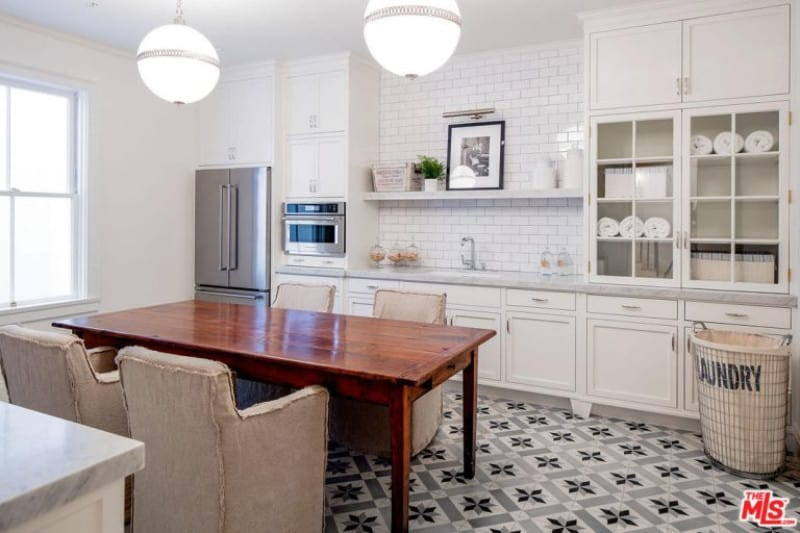 White dine-in kitchen with marble countertop and floating shelf fixed to the subway tile backsplash. It includes a rich wood dining table and beige skirted chairs lighted by a pair of glass globe pendants.