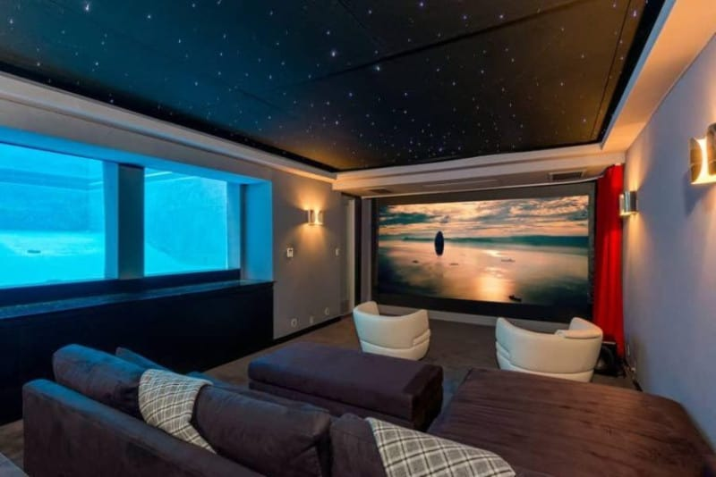 Stylish home theater with cozy theater seats and charming walls with wall lighting. The tray ceiling looks absolutely gorgeous.