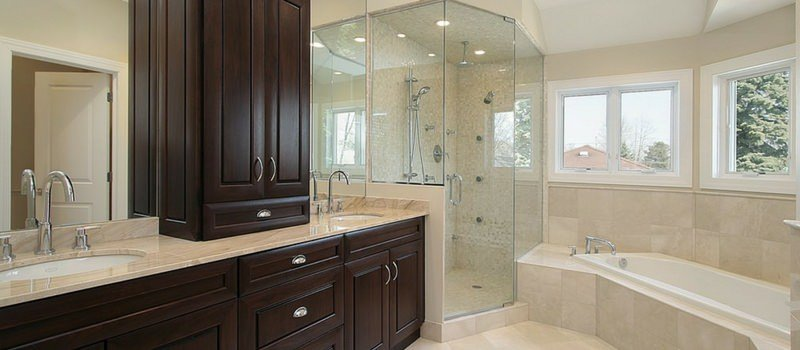 Spacious beige primary bathroom with glass-enclosed shower, a drop-in tub by the windows, and double vanity sink.