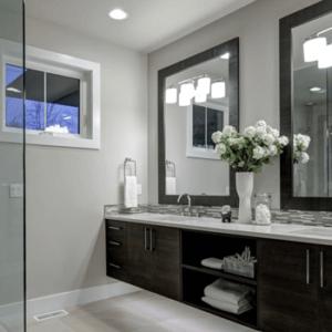 Gray bathroom with dark wood vanity and shower