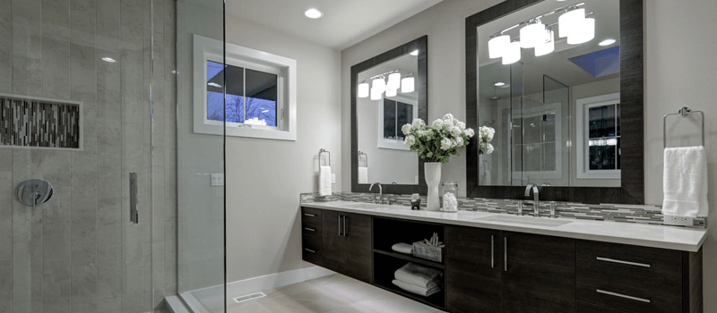 Gray bathroom with dark wood vanity and shower