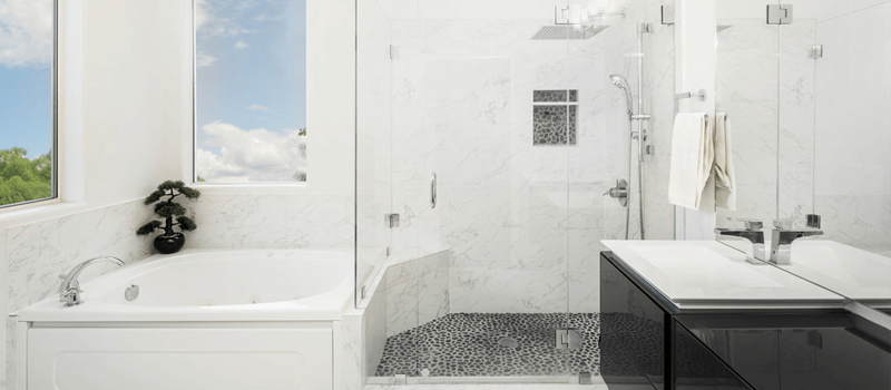 White bathroom with black vanity, soaker tub and walk-in shower.