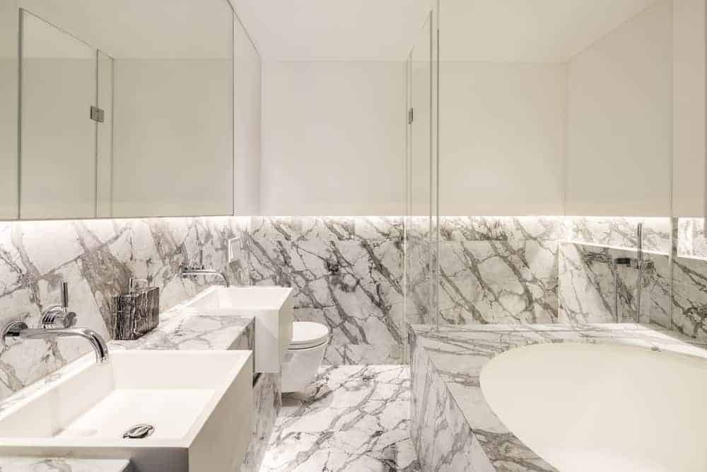This brilliant Asian-style bathroom is dominated by its white marble that has a slight charcoal tone to it. This complements the white bathtub, white rectangular sinks and the white floating toilet at the corner by the shower area covered in glass.