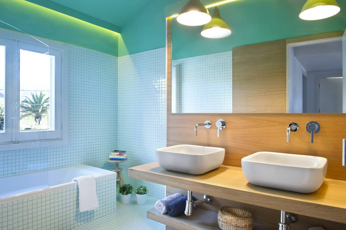The simplicity and beauty of this bathroom presents a distinctive Japanese flair with its wooden open vanity that supports the two white basins of the sink. This wooden structure extends to the frame of the large vanity mirror. Those wooden elements are complemented by the bright green tones of the tiles on the floor, walls and bathtub housing.