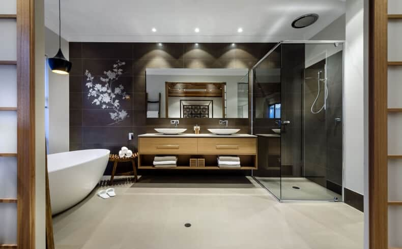 This charming and relaxing bathroom oozes with a zen aura. It has a white freestanding bathtub on the side topped with a black hanging pendant light matching with the black wall of the wooden floating vanity that is adorned with a mural of flowering branches. Beside this is the glass-enclosed shower area with the same black walls as the vanity.