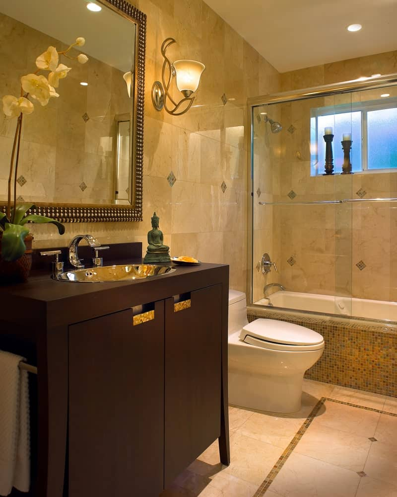 The glass-enclosed shower area has the same beige tiles on its walls as the rest of the bathroom. This is complemented by the dark wooden vanity trimmed with golden handles and silver basin and faucet. This is also accented with a small Buddha figurine.