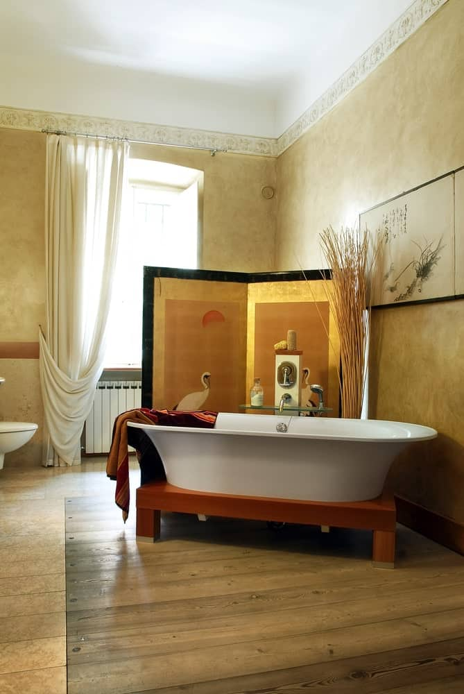 The freestanding white bathtub of this Asian-style bathroom is fitted with wooden legs that complements the beige walls and the room divider that has a stork artworks on it. This matches well with the wall-mounted artwork above the head of the bathtub.