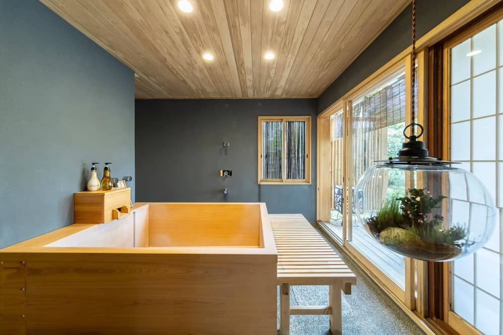 This Asian-style bathroom has a distinct Japanese charm to its wooden bathtub that stands out against the dark gray walls. This pairs well with the light wooden bench on the side that matches the wooden frames of the sliding doors as well as the wooden ceiling.