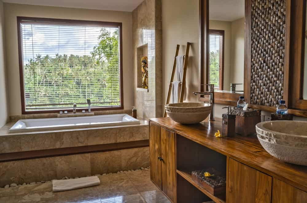 The lovely bathtub is in a relaxing nook by the window and adorned by a small alcove above the head that has a colorful Asian-style decor. This setup is punctuated by a wooden vanity with woven wicker accents on its vanity mirrors above the stone basin sinks.
