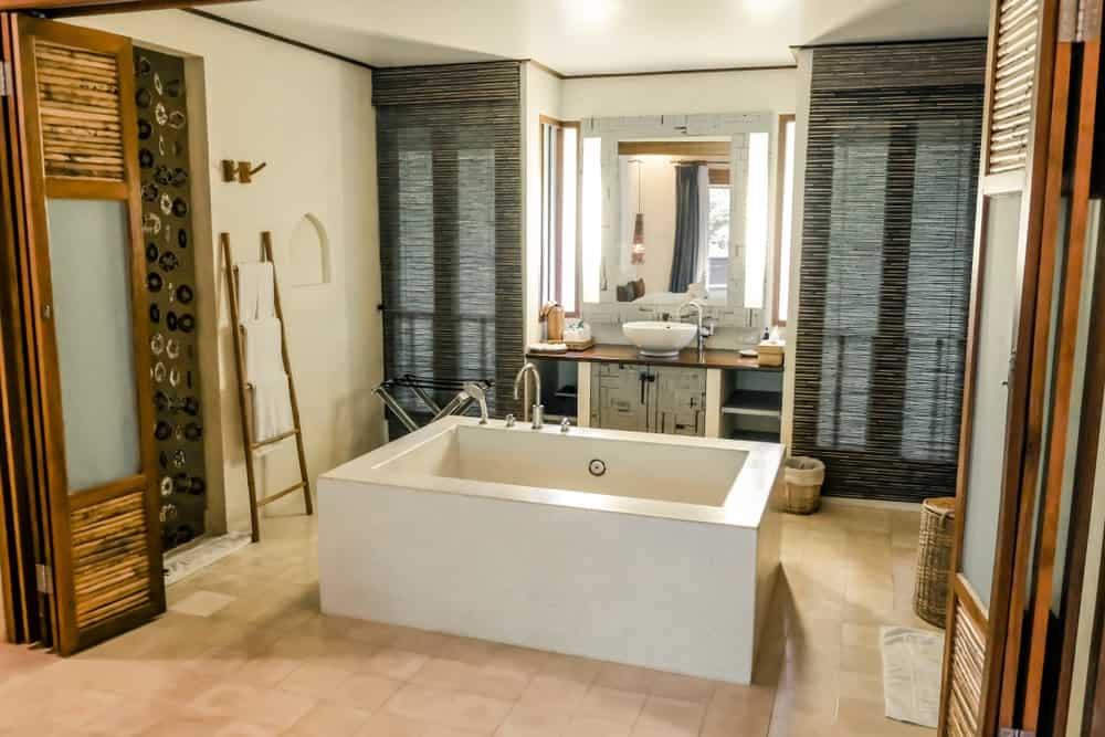 This charming Asian-style bathroom has a white bathtub in the middle of the beige floor tiles. Next to this is the bright vanity that is flanked by shaded glass windows. The folding wooden doors of this bathroom opens up to reveal a large entryway.