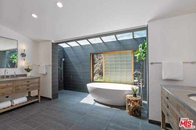 This is a spacious and bright bathroom with white walls and white ceiling on its vanity area that has two vanities across each other. These two flank a large entryway to the alcove of the freestanding bathtub that is adorned with a Japanese-style window made of shoji paper.