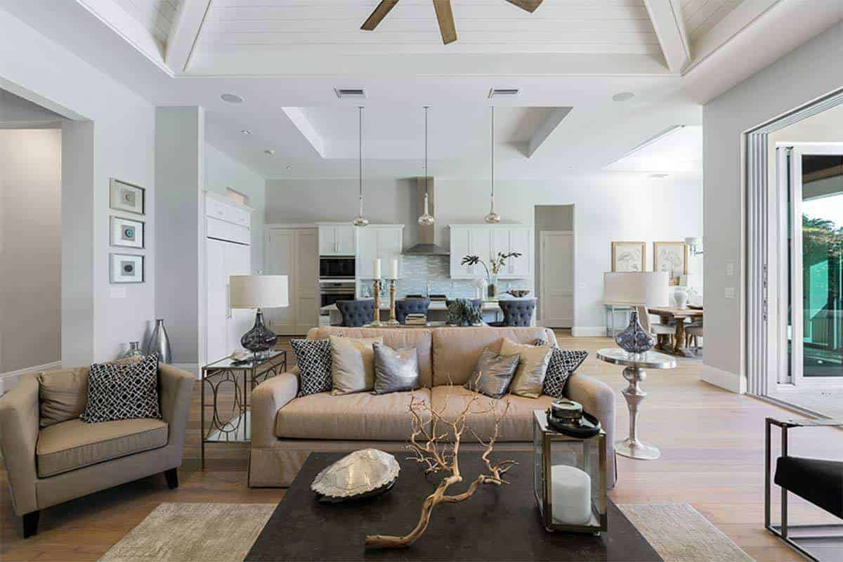The brown leather two-seat sofa and the cushioned armchair beside it matches well with the hardwood flooring that is topped with a light gray area rug under a black coffee table that contrasts the white arched ceiling.