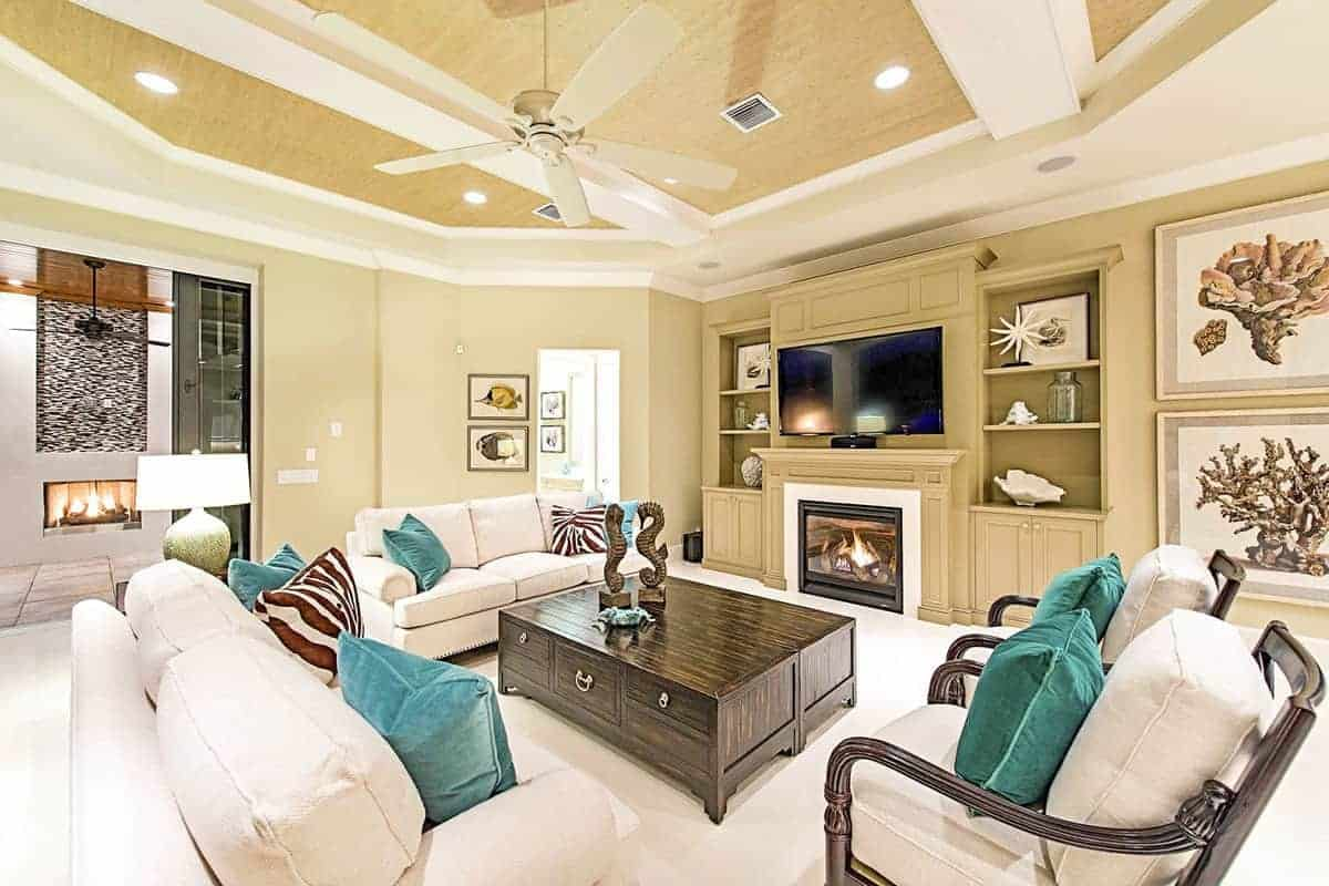 The white cushions of the sofas and armchairs blend with the carpeted flooring that makes the dark wooden coffee table stand out. This is complemented by the beige walls that blend with the large wooden structure housing the fireplace and the TV flanked by shelves.