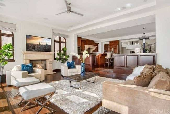 The TV is p-laced on the beige mantle of the fireplace that stands out against the stark white walls and ceiling with a modern ceiling fan in the middle over the wooden coffee table over the furry area rug covering the dark hardwood flooring.