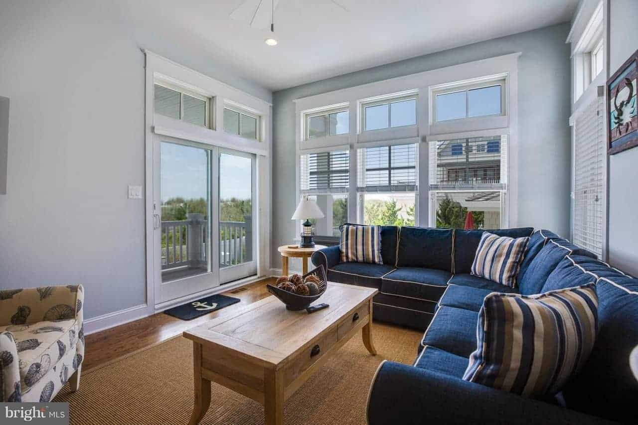 The dark hardwood flooring is dominated by the dark blue hue of the large L-shaped sectional sofa brightened by glass doors and windows facing a wooden coffee table that partners well with the woven area rug as well as the hardwood flooring.