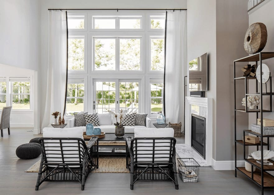 This bright and white living room is due to the high ceiling complemented by the tall glass windows that bring in an abundance of natural lighting. The furniture are simple black and white to complement this setup and is given a fireplace with a white mantle for a bit of warmth.