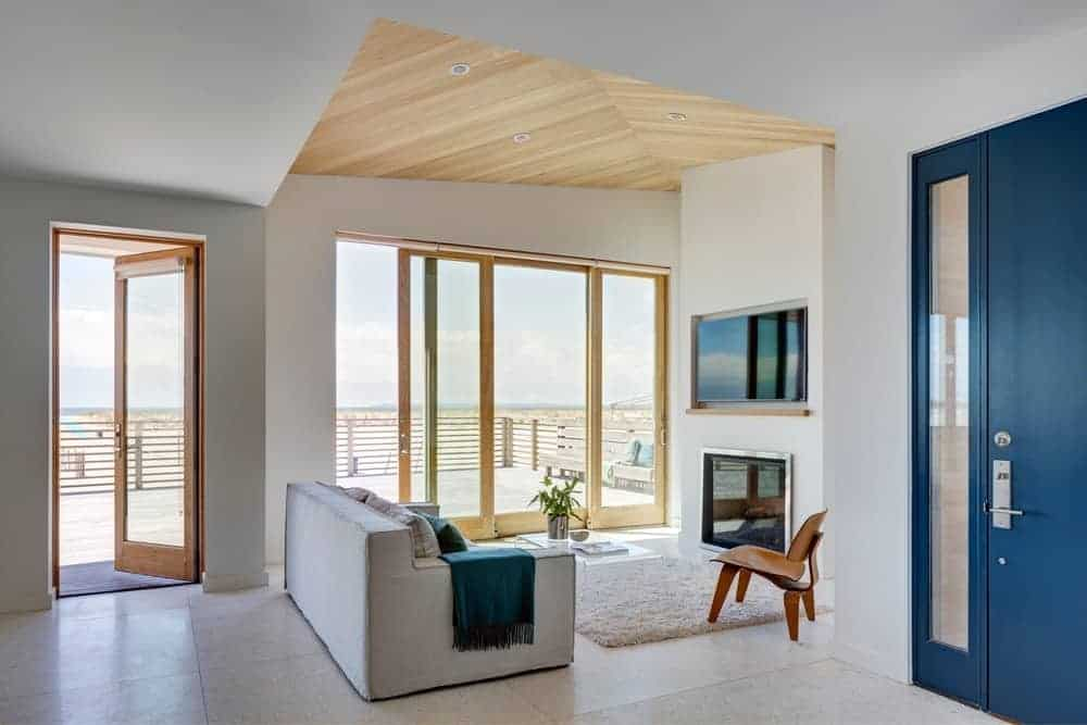 This is a simple Beach-style living room with a single light gray sofa paired with a white area rug facing a white wall that houses the modern fireplace and the TV above it. This is paired with a great background of seaside view through glass doors.