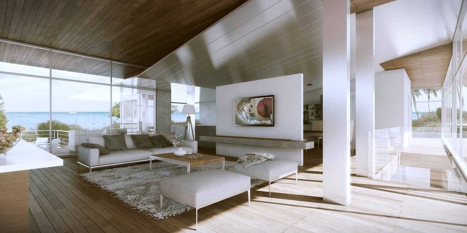 This wide living room is further brightened by the glass walls that feature a nice seaside view bringing with it an abundance of natural lights for the hardwood flooring that paired with the wide ceiling contrasted by the white modern sofa set and the white support pillars.