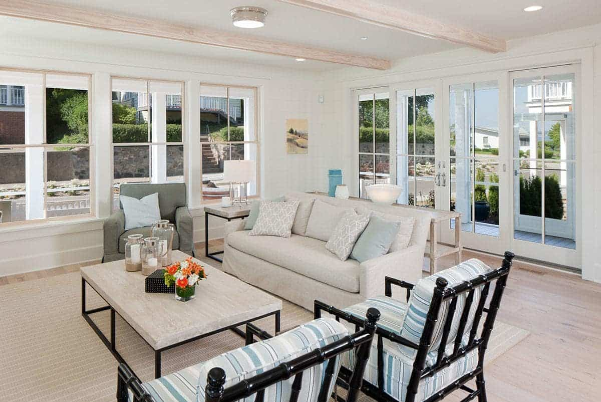 The exposed wooden beams of the white ceiling matches well with the hardwood flooring that is covered with a woven area rug under the beige sofa and the two dark bamboo armchairs with blue-striped cushions.