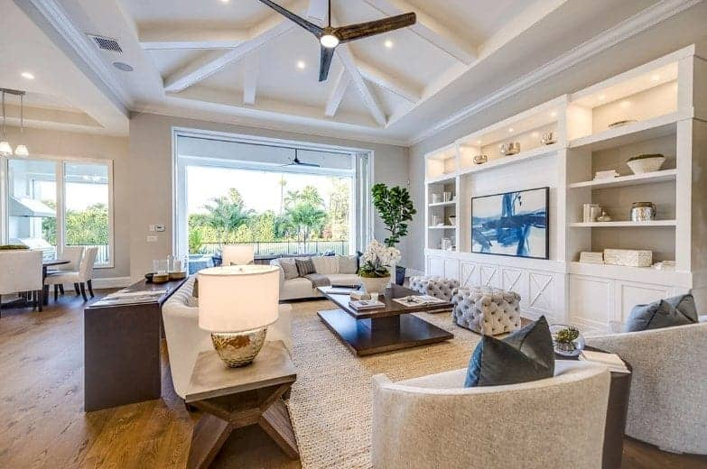 The white arched ceiling has exposed wooden beams that pairs perfectly with the large white wooden structure dominating the wall that has shelves flanking the mounted TV. Facing this is the beige couches and gray armchairs over a woven area rug.