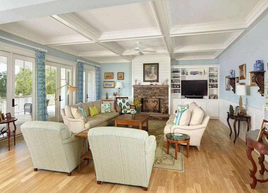 This bright and airy living room has a white coffered ceiling complemented by light blue walls with a white wooden wainscoting before the hardwood flooring that complements the stone inlay of the fireplace across from the beige sofa set.