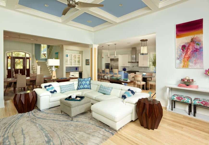 The U-shaped white sectional sofa has blue patterned pillows on it that matches with the coffered ceiling as well as the blue and gray area rug over the light hardwood flooring that contrasts the dark wooden end tables.