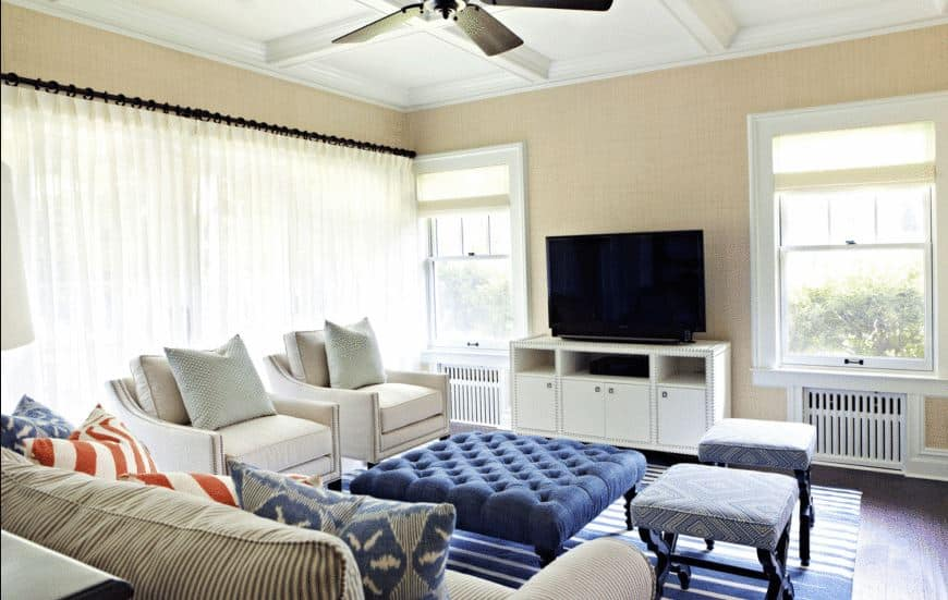 The coffee table is upholstered with blue cushions that has a button tufted finish. This is a nice pairing with the blue striped area rug over the dark hardwood flooring that contrasts the beige walls and white coffered ceiling.