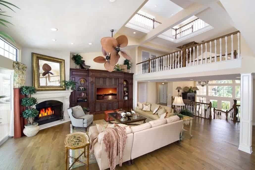The fireplace is inlaid with a white mantle that contrasts the dark wooden structure beside it housing the TV. This is a nice complement to the hardwood flooring topped with a light hued area rug that complements the various sofas and armchair.