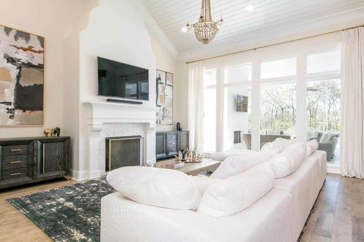 The large white cushioned sectional sofa is complemented by the gray industrial-style area rug over the hardwood flooring. It also complements the white fireplace with a white mantle above it is the mounted TV flanked by large colorful paintings.