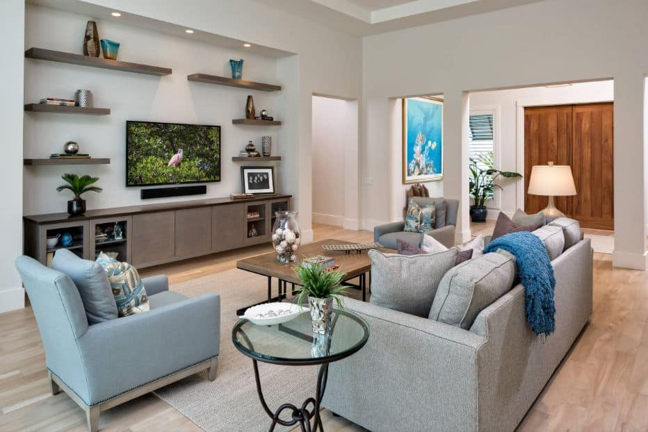 The charming light green sofa set is facing a light gray wall with wall-mounted shelves on it surrounding the wall-mounted TV over a low long cabinet that matches with the wooden coffee table.