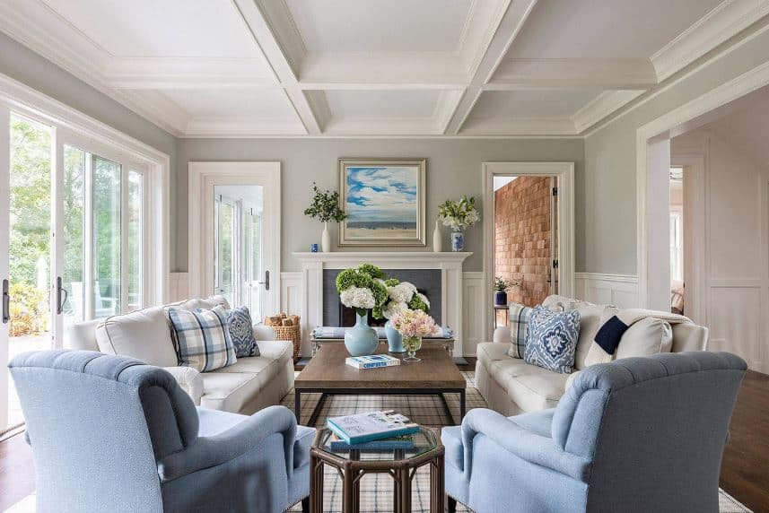 The white coffered ceiling is complemented by the light gray walls that match with the light gray sofas illuminated by the natural lights coming in from the glass sliding doors adjacent from a two glass doors flanking the fireplace.