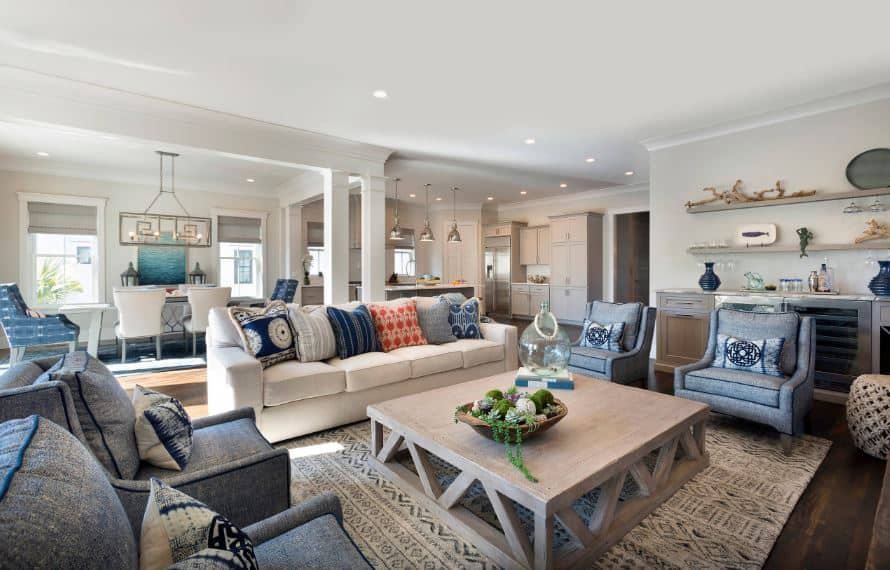 The wooden coffee table over the light gray patterned area rug is surrounded by four blue-gray cushioned armchairs with blue patterned pillows that stands out against the light gray walls and white ceiling with recessed lights.