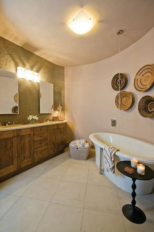 This master bathroom is decorated with interesting round wall arts that hung above the freestanding tub accompanied by a black side table. It includes a natural wood vanity paired with frameless mirrors and glass sconces.