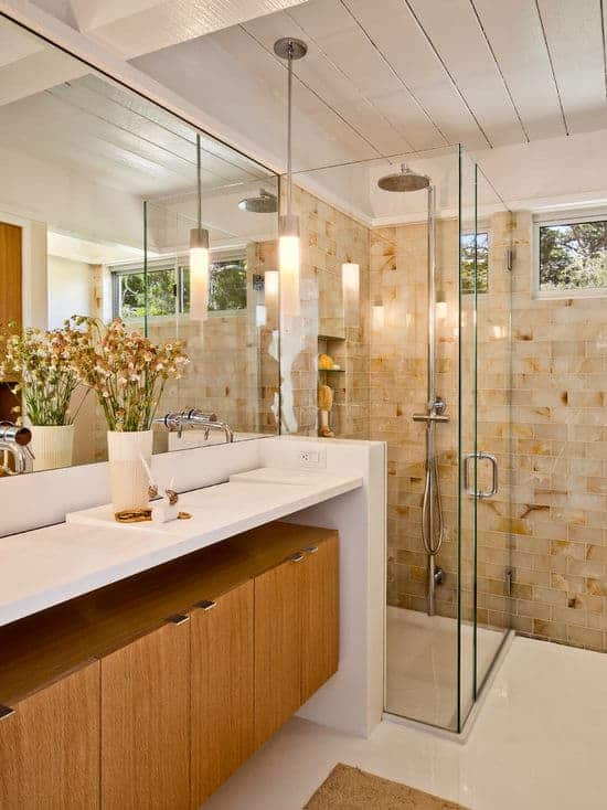 Midcentury bathroom boasts a single sink vanity illuminated by a cylindrical pendant that hung from the wood beam ceiling. Elegant brick marble tiles from the walk-in shower add personality to the room.