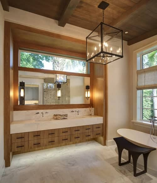 Contemporary bathroom illuminated by a cube pendant light that hung from the wood beam ceiling. It has a floating dual sink vanity and a freestanding tub paired with a cast iron stool.