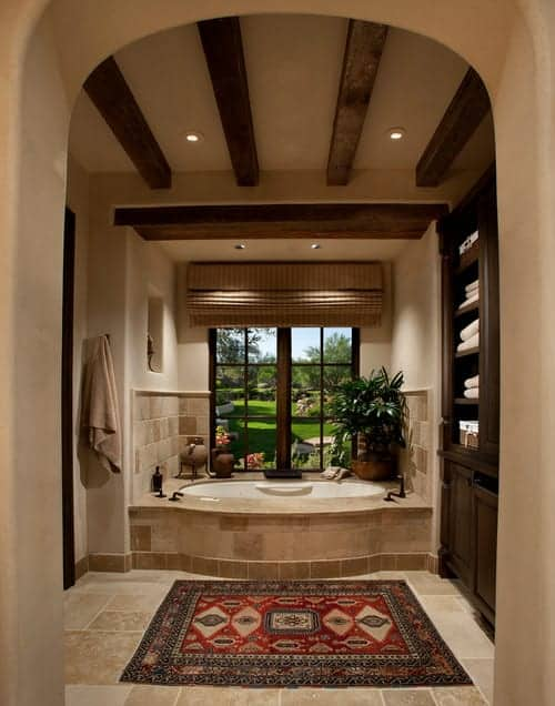 A patterned red rug lays on the limestone flooring in this beige bathroom with dark wood storage cabinet and a deep soaking tub by the wooden framed window overlooking the lush green outdoor.