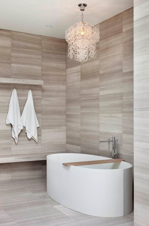 Beige bathroom with tiled flooring and walls mounted with matching shelf and seat for a unified look. It includes a freestanding tub lighted by a fancy chandelier.
