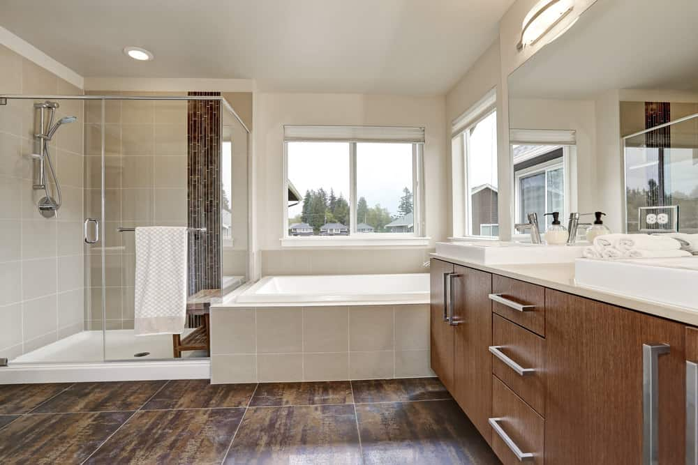 Natural light streams in through the glazed windows in this master bathroom with wooden sink vanity adjacent to the deep soaking tub and walk-in shower enclosed in frameless glass.