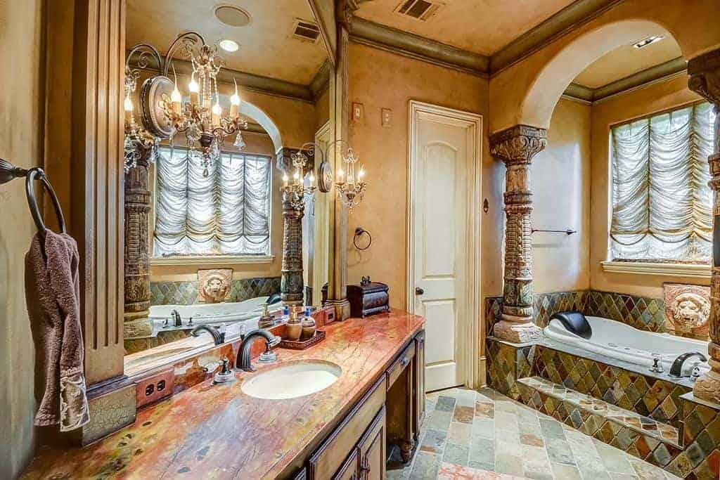 Mediterranean bathroom integrated with an eclectic design. It has a wooden sink vanity lighted by classy sconces mounted on the mirror and an alcove tub lined with carved columns.