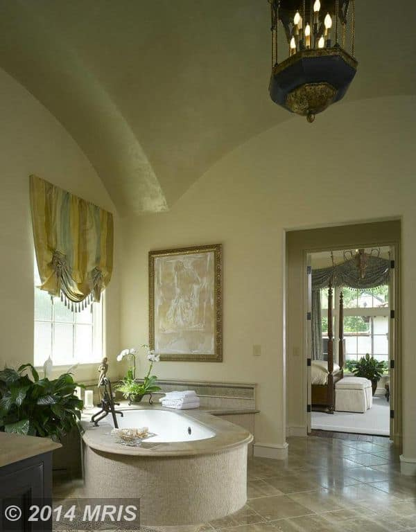 Tropical bathroom with gold framed wall art and an oval-shaped bathtub lighted by a stylish candle pendant that hung from the arched ceiling.
