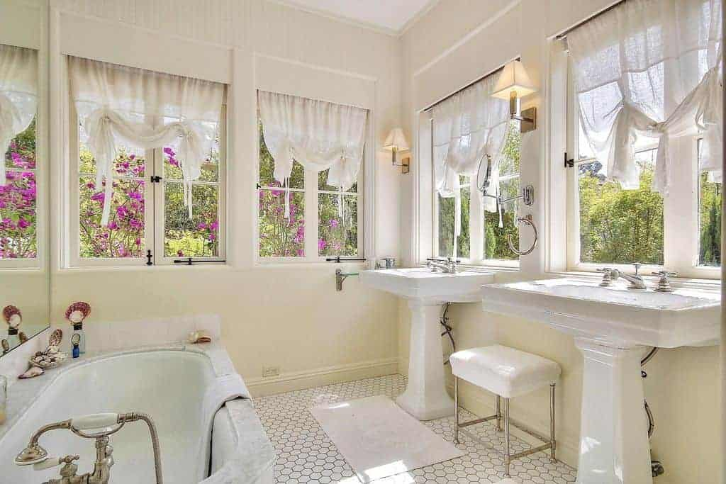 Light and airy primary bathroom with hex tile flooring and glazed windows dressed in white sheer curtains. It includes a marble bathtub and metal stool that sits in between sink pedestals.