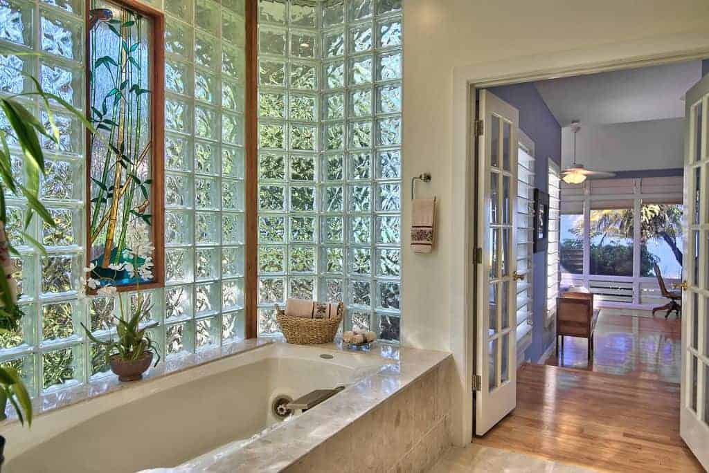 Fresh primary bathroom with a French door and glass block window accented by a gorgeous stained glass panel. It offers a deep soaking tub clad in marble tiles that match the flooring.
